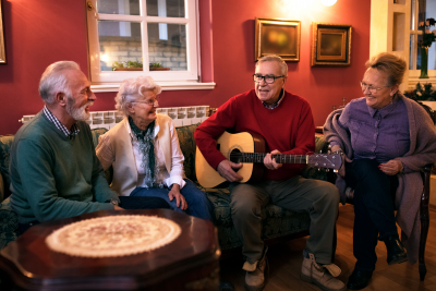 senior men playing guitar with his friends