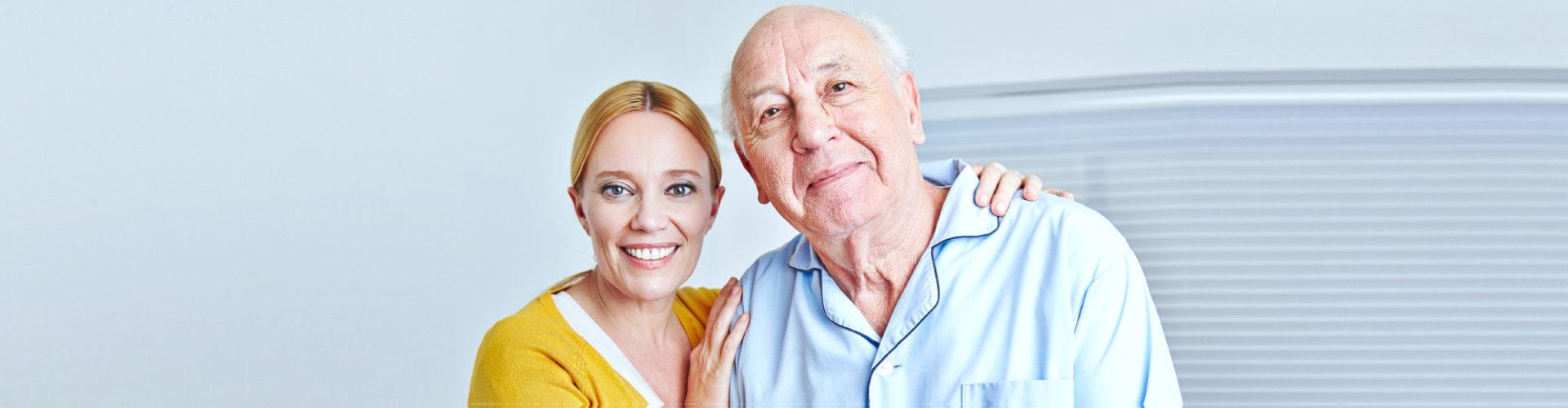 senior man with caregiver smiling