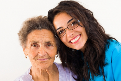 caregiver smiling together with senior woman
