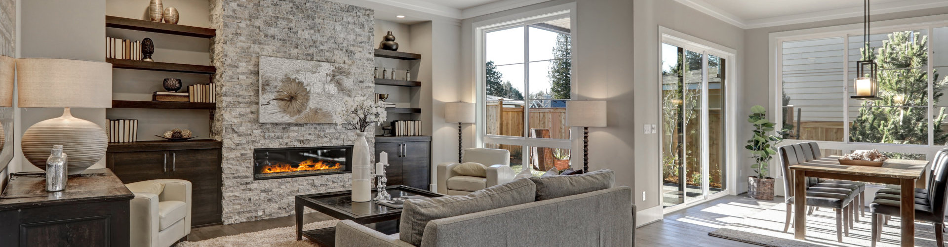 living room interior in gray and brown colors features gray sofa atop dark hardwood floors facing stone fireplace with built-in shelves